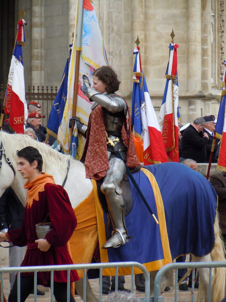 The lucky young woman chosen to portray Joan in the 2013 Orléans festival waves at the crowd; photo by the author.